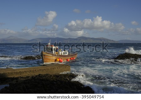 Passenger boat approaching the landing jetty on Isle of Staffa, Scotland with the Isle of Mull in background.