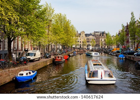 Passenger boats on canal tour in the city of Amsterdam, Holland. - stock photo
