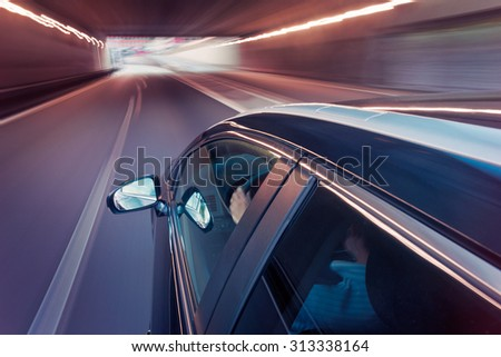 Passenger car, seen from the side of the roof, driving in the middle lane of a motorway, driving through a tunnel - stock photo
