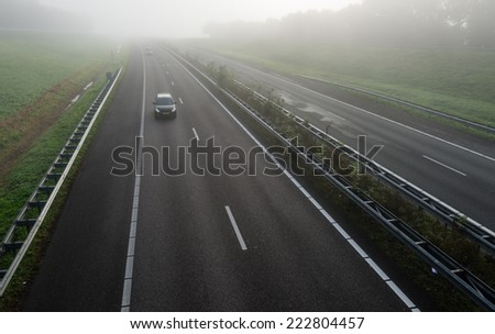 Passenger cars with burning headlights driving on a freeway in the Netherlands early on a foggy morning in the fall season.