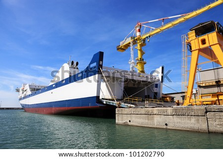 passenger ferry in harbor with door open to take cars - stock photo