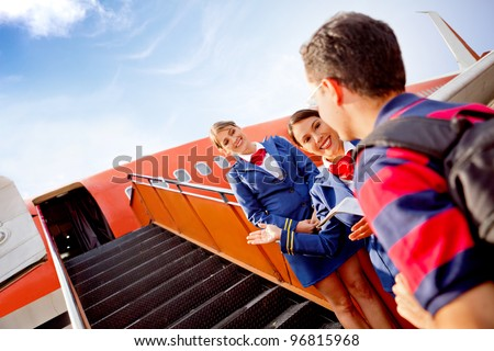 Passenger going into the airplane and air hostesses welcoming him - stock photo