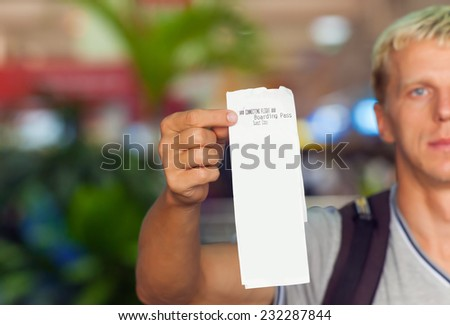 passenger holding in his hand a boarding pass template - stock photo
