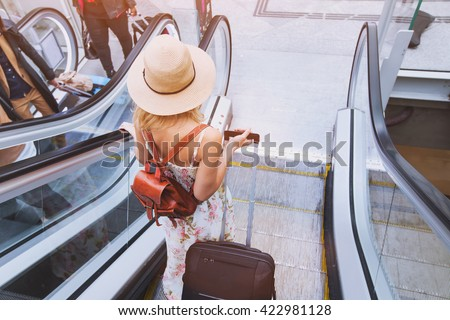 passenger in airport or modern train station, woman commuter travels with luggage - stock photo