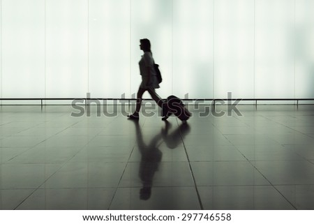 passenger in the interior of the airport carrying a troley - stock photo
