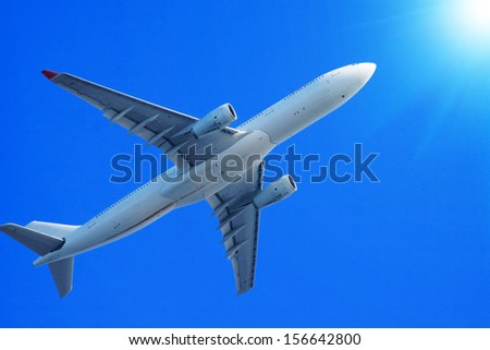 Passenger jet air plane flying on blue sky - stock photo