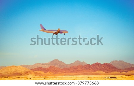 Passenger jet air plane flying on blue sky over the land mountains - stock photo