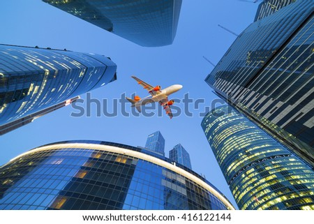 Passenger jet airplane flies above skyscrapers in financial district of Russian capital aka Moscow City.