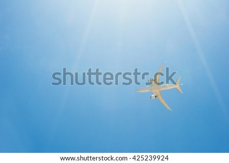 Passenger jet airplane flying on blue sky with sunlight - stock photo