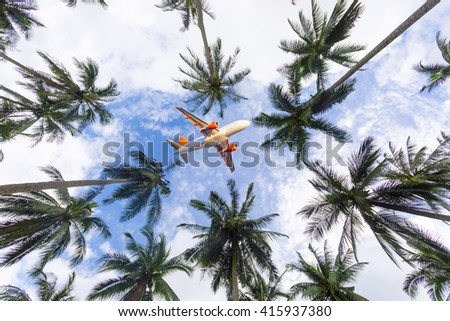 Passenger jet airplane in sky above palm trees at tropical resort.
