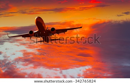 Passenger jet plane flies above the clouds - stock photo