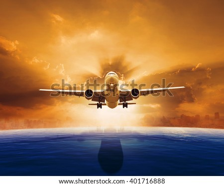 passenger jet plane flying over beautiful sea level with sun set sky above and urban skyline behind - stock photo