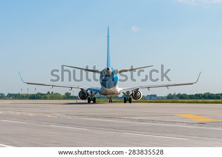 Passenger jet plane on the runway in the airport. Back view. Travel background - stock photo