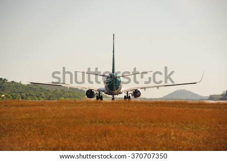 Passenger jet plane on the runway in the airport. Back view. Travel background