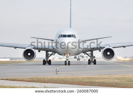 Passenger jet plane on the runway in the airport (front view) - stock photo