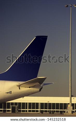 Passenger jet tailplane against airport terminal - stock photo