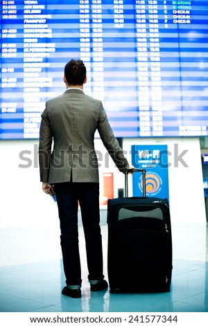 passenger looking at timetable board at the airport - stock photo