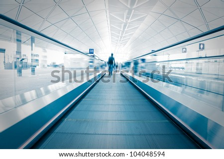 passenger (Man) rushing through an escalator in airport terminal, blue tone - stock photo