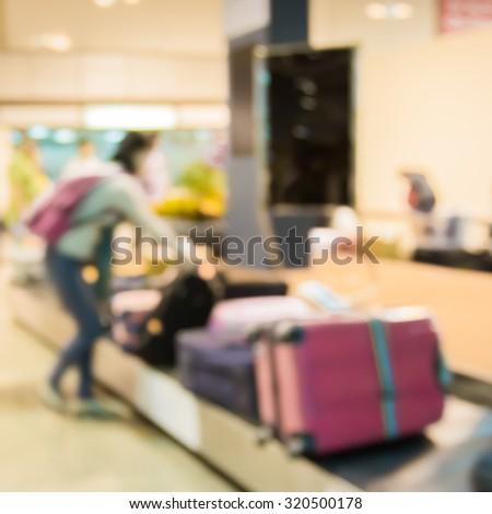 passenger picking luggage on conveyor belt in airport,blur motion - stock photo
