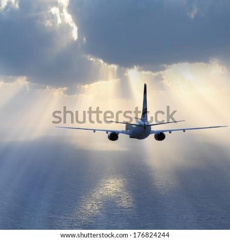 Passenger plane flies above the ocean. - stock photo