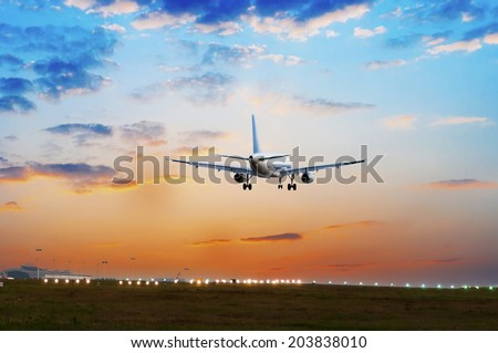 passenger plane fly up over take-off runway from airport at sunset