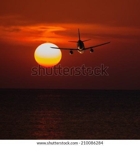 Passenger plane flying at a low altitude at sunset and the sun background - stock photo
