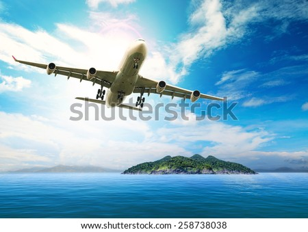 passenger plane flying over beautiful blue ocean and island in purity destination sea beach use for summer holiday vacation traveling - stock photo