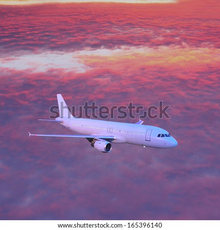 Passenger plane in the sky above the clouds at sunset. - stock photo
