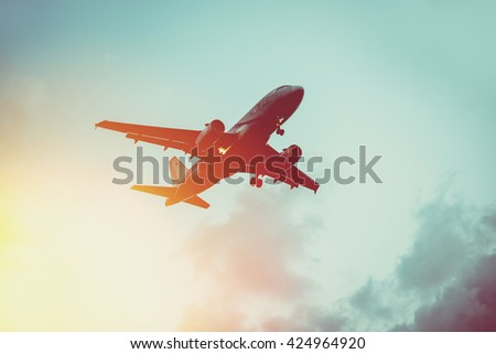 Passenger plane in the sky at sunrise or sunset. Vacation and travel concept. Toned image - stock photo