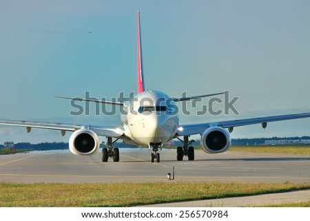 Passenger plane jet taxiing along the runway - stock photo