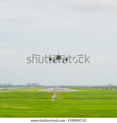 passenger plane landing on runway - stock photo