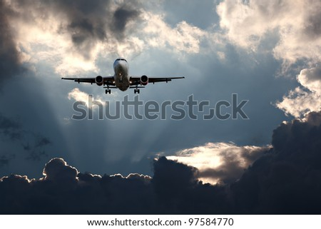 Passenger plane on final approach, against a stormy sky - stock photo