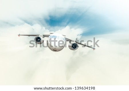 Passenger plane with cockpit and engines in front view flying high in blue cloudy sky. Comfortable and fast travelling by air. Business and touristic trips. Aviation and aircraft.