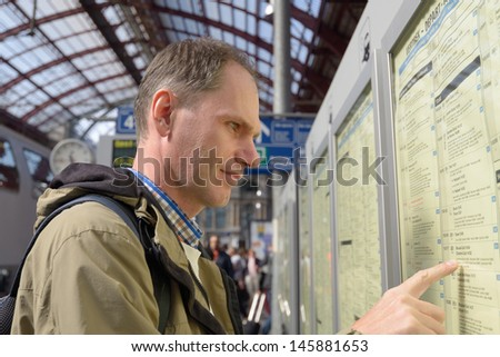 Passenger search the train in the timetable on a train station of Antwerp, Belgium