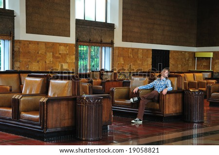 Passenger sleeps in the waiting room of Union Station in Los Angeles - stock photo
