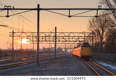 Passenger train and railroad tracks during a nice sunrise.