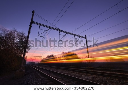 Passenger train on railroad tracks at the sunrise - blurred motion - stock photo