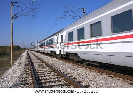 Passenger train passing railroad on a sunny day - stock photo