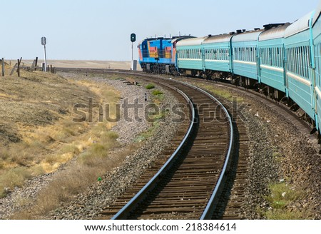 Passenger train passing railroad on a sunny day in Central Asia. - stock photo