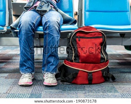 Passenger traveler woman in airport waiting for air travel with backpack - stock photo