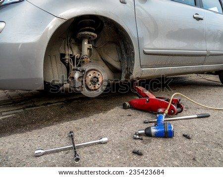 Passenger vehicle on lift with front tire removed - stock photo