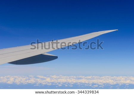 Passenger view from airplane flying over clouds - stock photo