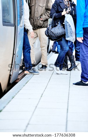 Passengers departs commuter train - stock photo