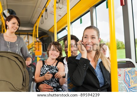 Passengers in a bus - a commuter, a woman with a stroller, a man - stock photo