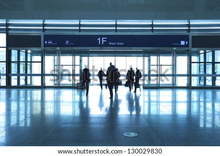 Passengers in a hurry to walk the modern airport interior gate