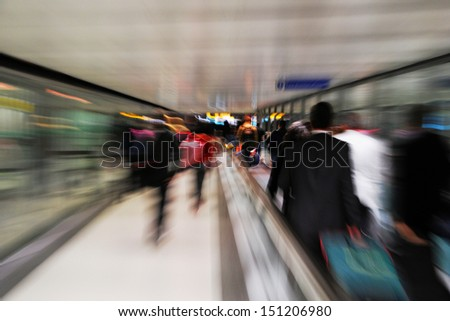 passengers in a rush at an international airport (intentional blur motion) - stock photo