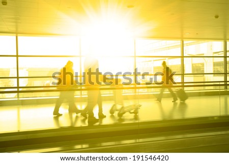 Passengers in modern airport interior glass wall aisle windows of people - stock photo