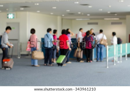passengers in row waiting check-in counters at airport on blur background - stock photo