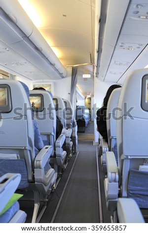 Passengers in the tourist class sitting in their seats of the airplane