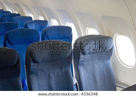 Passengers inside an airplane going to their aircraft seats